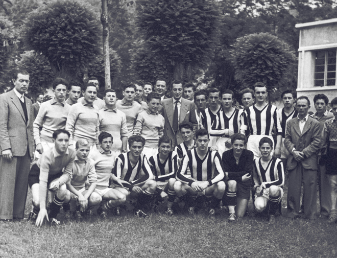 "Posing with a football team at the Headquarters of the ""Società Agricola Operaia di M.S. "" of Villar Perosa."